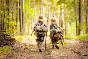 Two boys go hiking with backpacks on a forest road bright sunny day